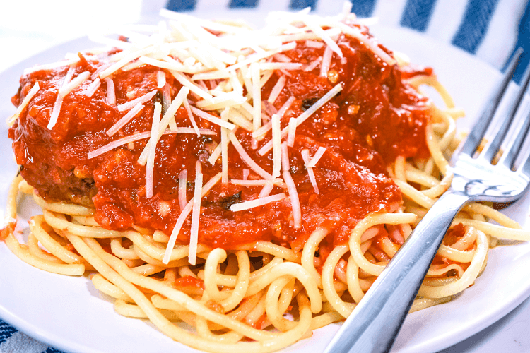 A white plate of spaghetti and meatballs covered in homemade sauce and fresh parmesan cheese.