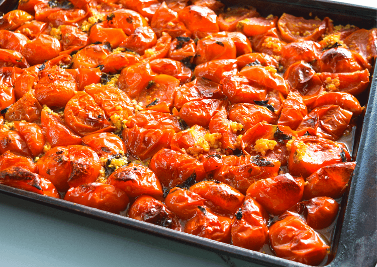 A pan of roasted tomatoes fresh out of the oven with little charred bits.