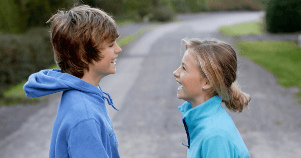 Tween boy and girl facing each other on a gravel road and laughing.
