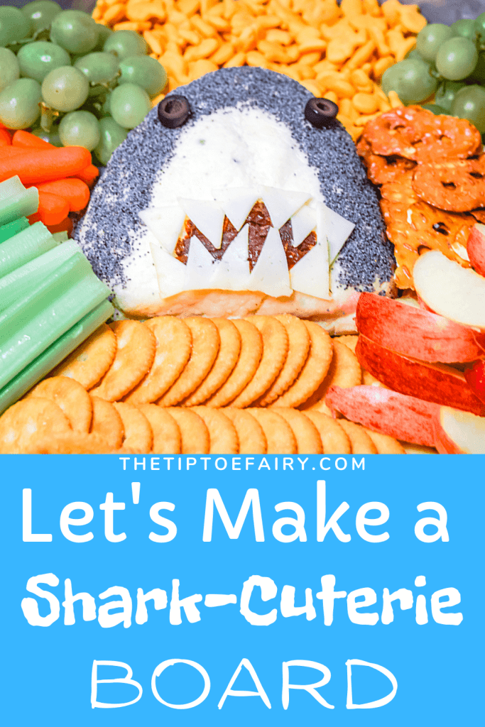 Close of a Shark Cheese Ball surrounded by crackers, veggies and fruit.