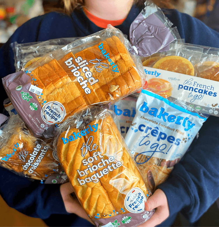 A young girl in a sweatshirt holding several bakerly bread products in her arms.