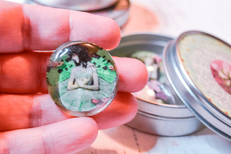 Close up image of a finished vintage DIY Magnet made from a cabachon, vintage image, and ceramic magnet in a hand.