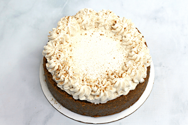 Finished image of the whole instant pot pumpkin cheesecake with piped cinnamon whipped cream.