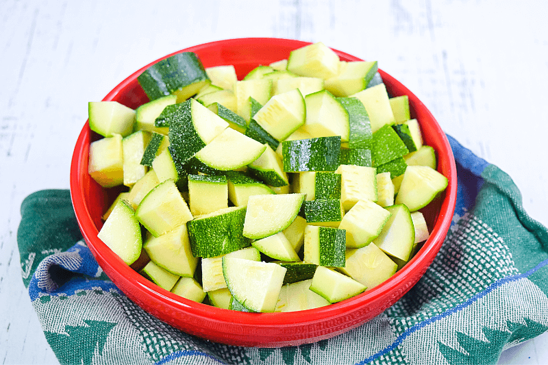 A red bowl full of cubed raw zucchini pieces.