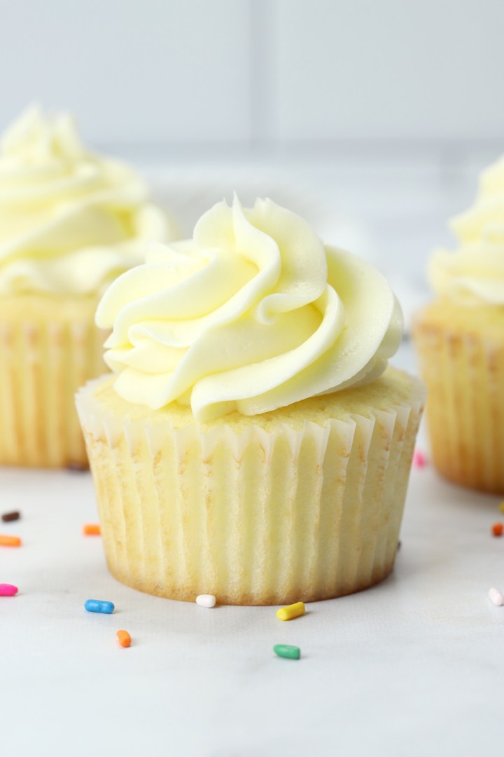 Close up of a vanilla cupcake with rainbow sprinkles on the counter.
