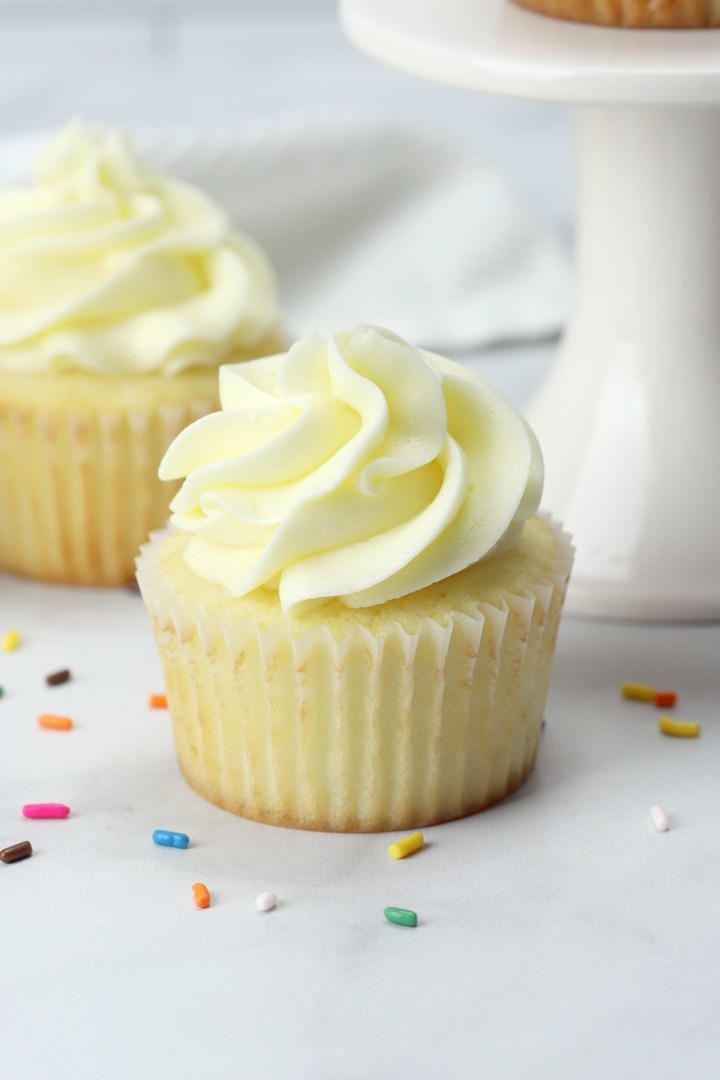 A homemade vanilla cupcake in a white wrapper.