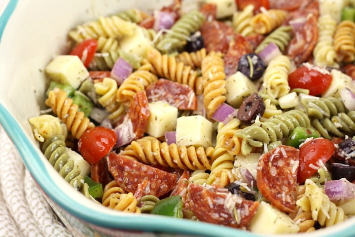 A close up of classic pasta salad in a bowl, made with tri-color rotini pasta.