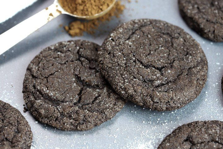 Close up of two dutch cocoa cookies and a tablespoon of cocoa powder