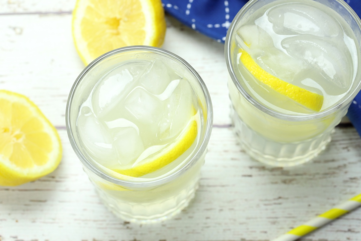 Two glasses of lemonade on a wooden counter top