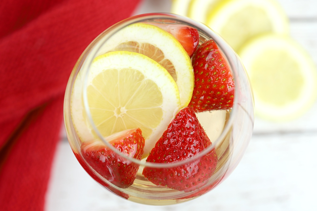 Strawberry slices and lemon slices floating in a wine glass