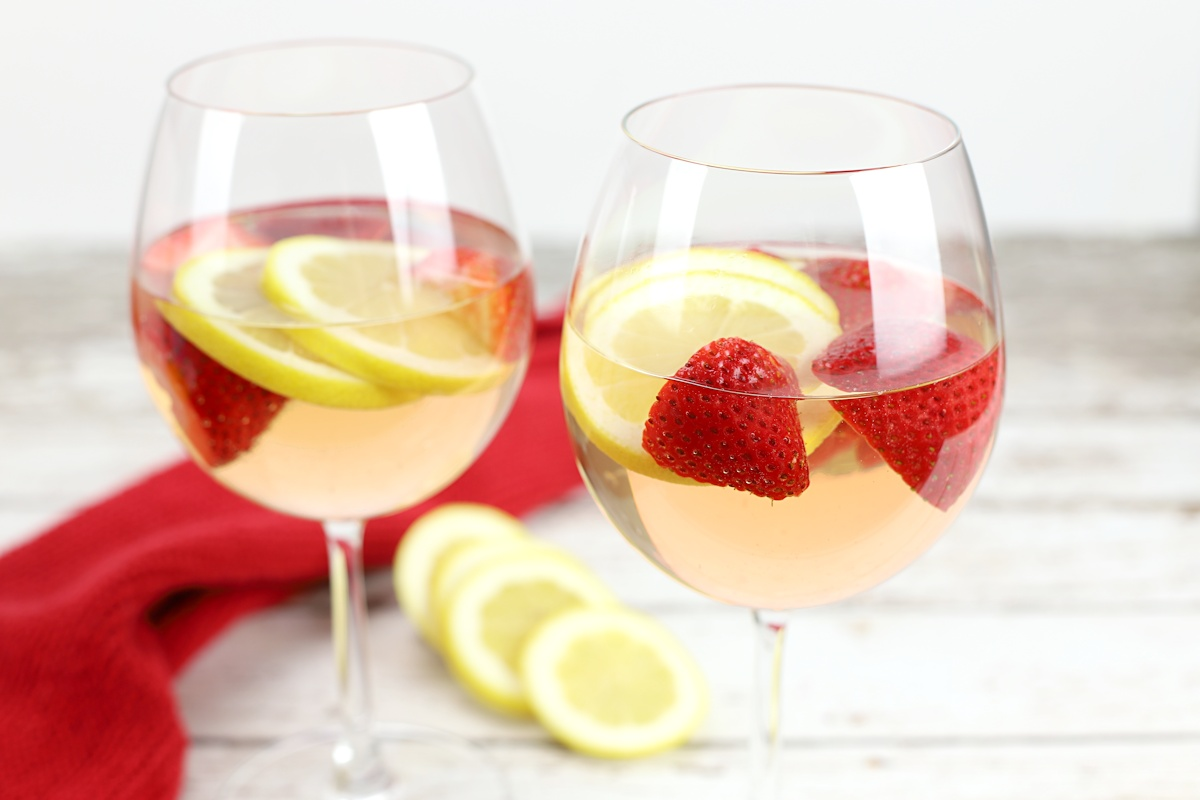 Two glasses of strawberry lemon rose sangria with lemon slices in the background.
