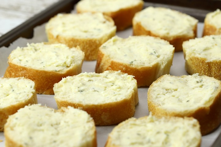 Slices of garlic bread on a baking sheet.
