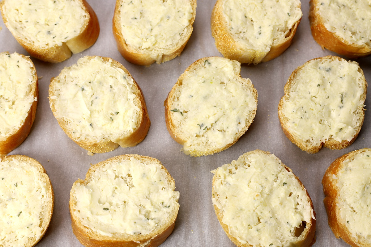 Slices of bread slathered in a cheesy butter spread.