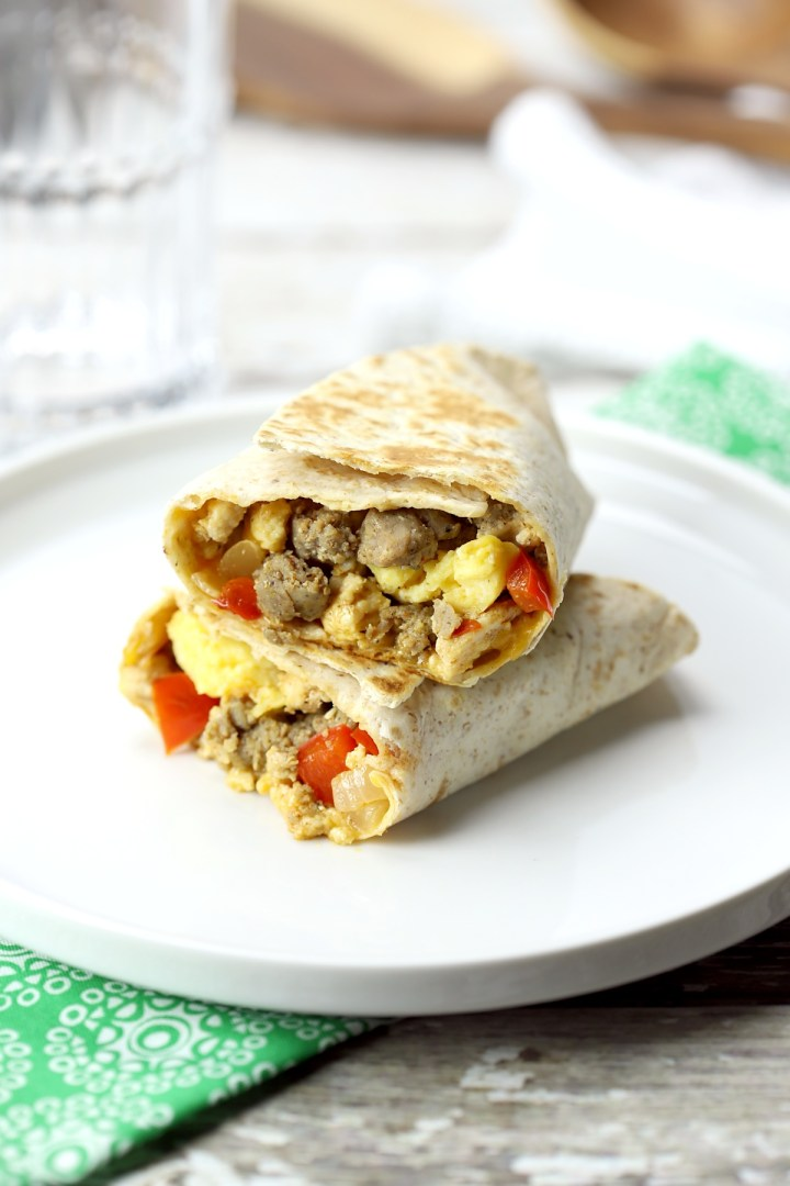 Breakfast burrito on a white plate, sliced in half to show filling.