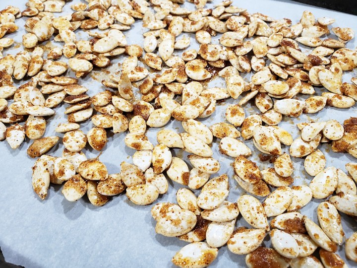 Pumpkin seeds spread onto a baking sheet.