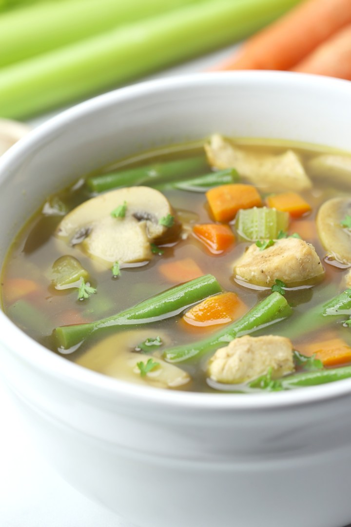 White bowl with chicken vegetable soup.