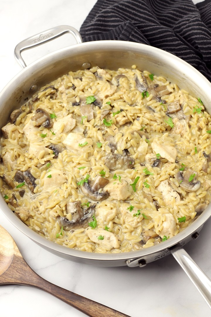 A saute pan filled with chicken, mushrooms, and orzo pasta.