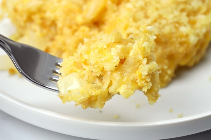 Close up of hash brown casserole on a fork.