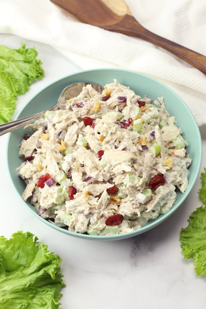 A blue bowl filled with chicken salad.