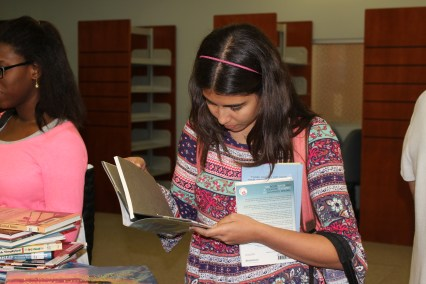 Junior Sierra Molina reads the front cover of one of the many books that the library decided to give away on March 28. The media center is undergoing a remodel that will turn the room into a more interactive and comfortable space with updated technology and newer books.