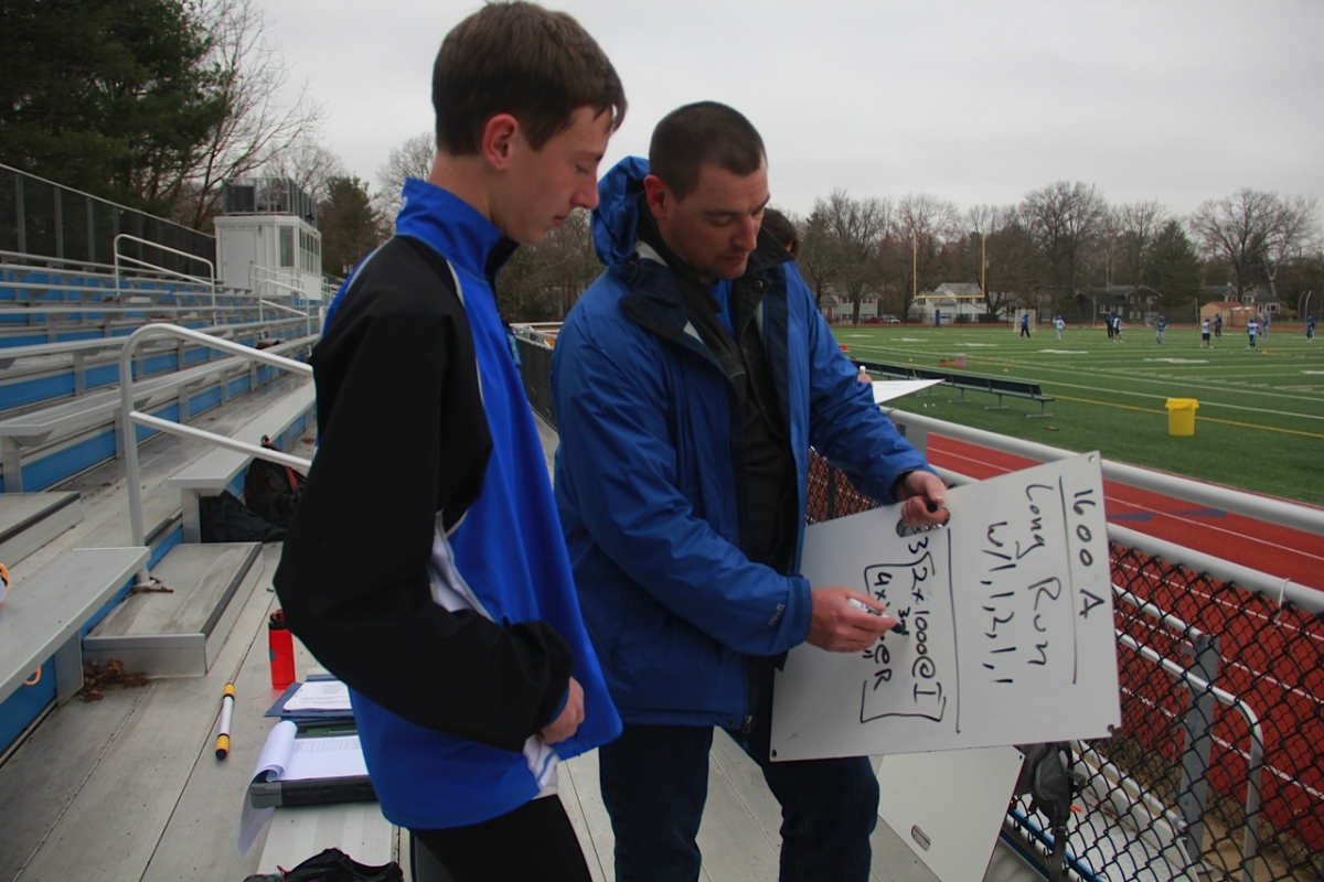 Girls and distance Head Coach James Smirk consults Alexander Roth '17 after the workout on April 9.  photo: Amy Wang