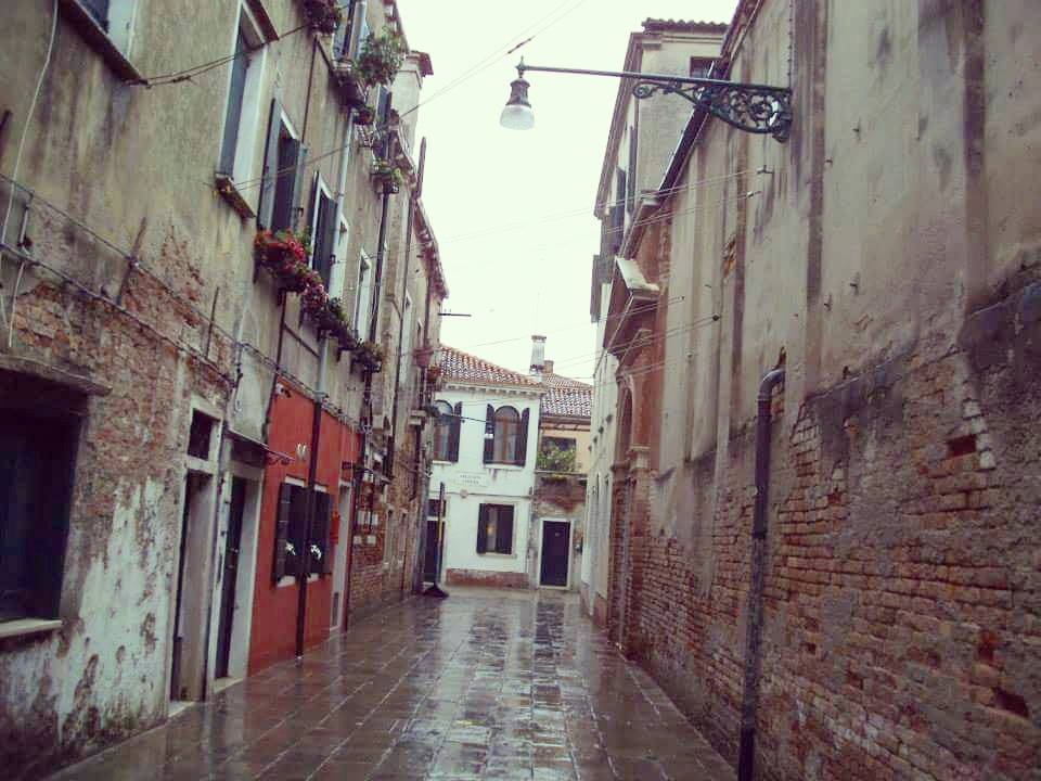 A small backstreet in Venice with tall buildings on either side in the rain
