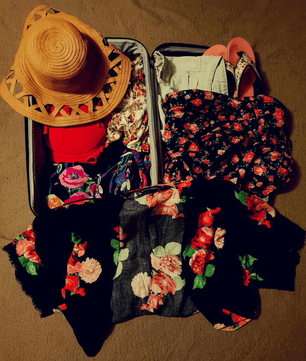 A purple suitcase with carry-on packing for Cyprus. A brown sunhat, red bikini, black and red dress, black and red kimono, white flowery dress, pink flip-flops and blue shorts.
