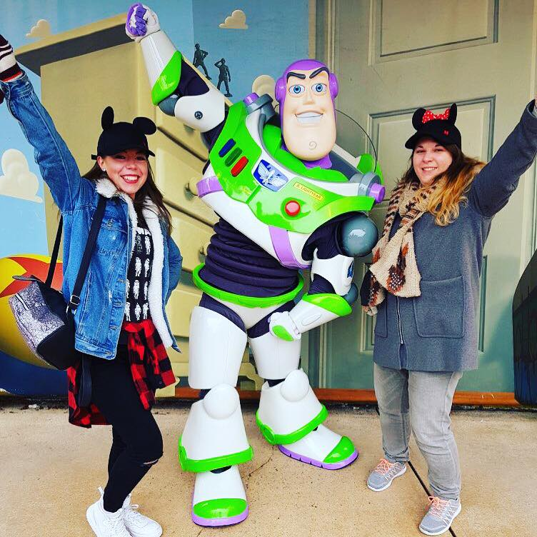 2 girls wearing Mickey ear hats posing with their arms in the air with Buzz Lightyear at his Character meet and greets