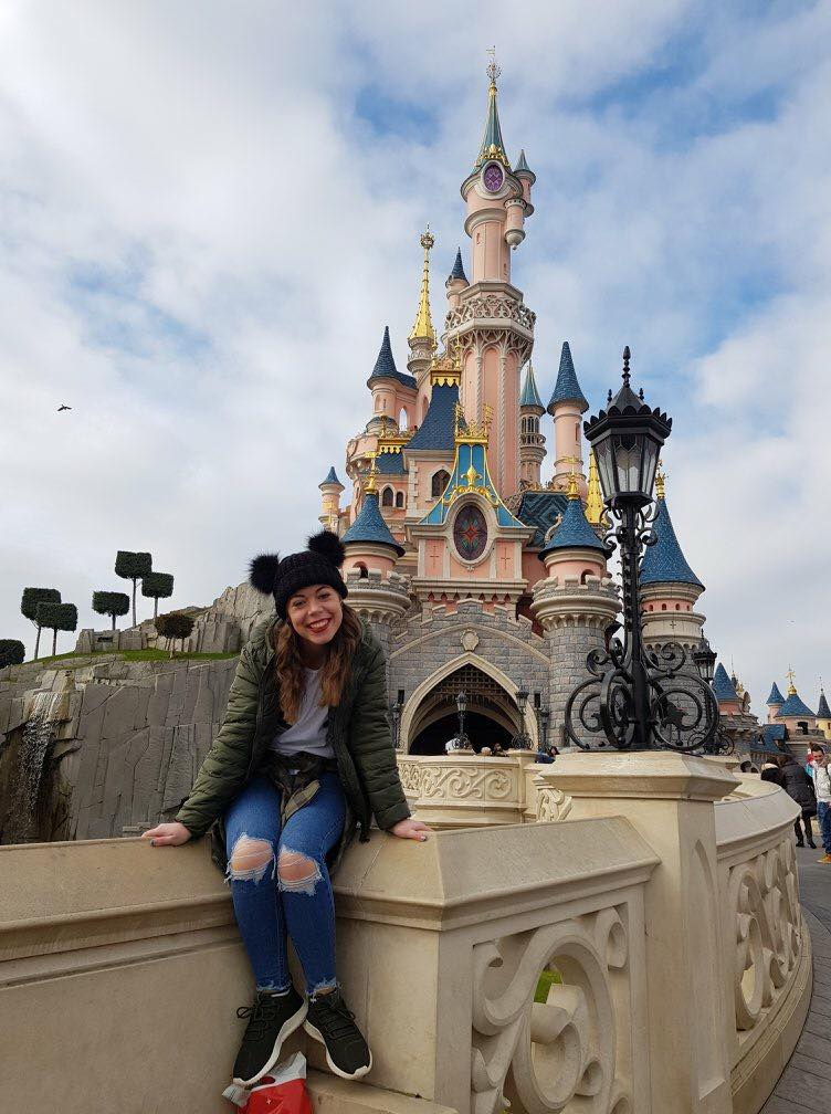 A girl with Mickey mouse hat sat on the wall in front of the pink sleeping Beauty's castle at Disneyland Paris