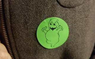Green circular sticker with a cartoon ghost on it