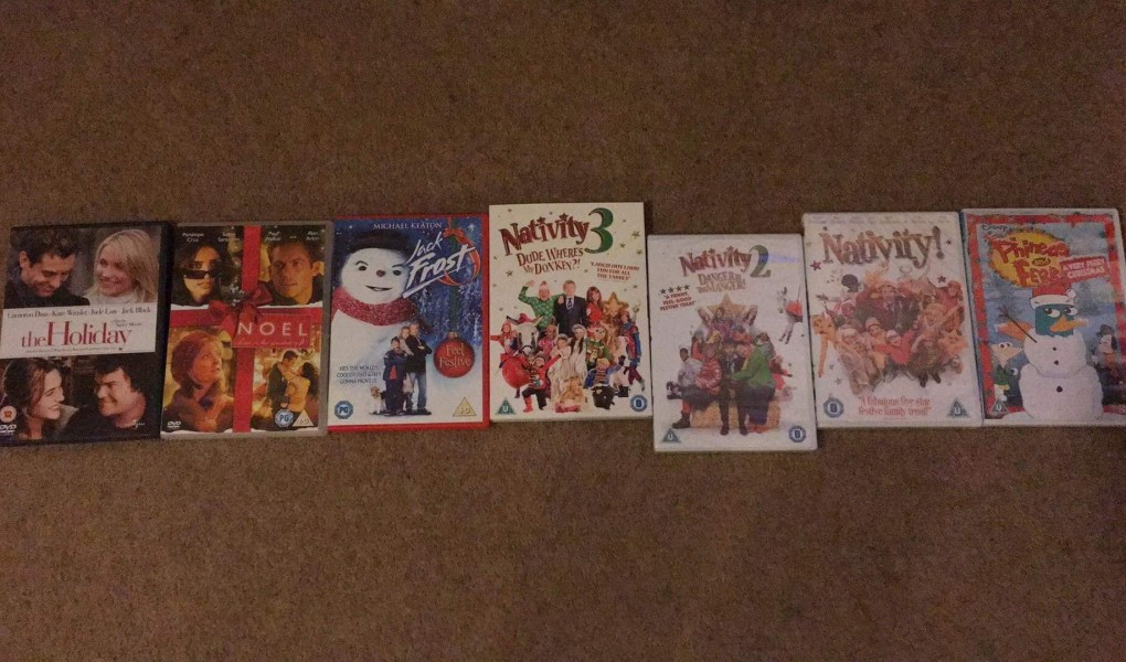 DVD boxes of Christmas films layed out. The films are The Holiday, Noel, Jack Frost, Nativity! Nativity 2, Nativity 3 and Phineas and Ferb the movie.