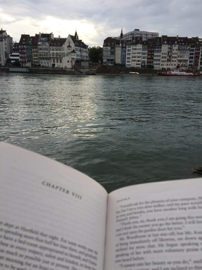 Reading a book while sat on the edge of the river Rhine with buildings on the other bank