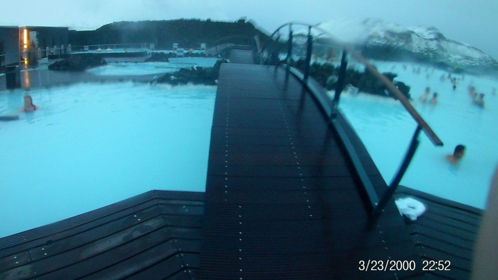 A wooden bridge over blue water between islands made of volcanic rock at the Blue Lagoon Iceland