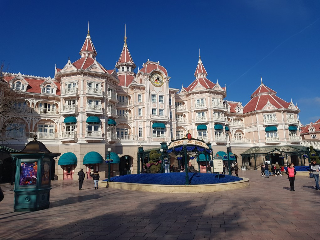 The Disneyland Paris Hotel over the entrance to Disneyland Paris. It is a pale pink, castle shaped building with dark pink roofs, green window covers along the walls and a flower bed with a mickey mouse head made of plants