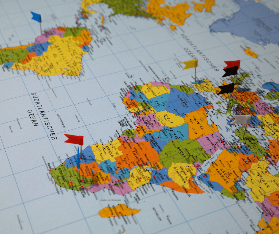 A colourful map of the world with flags stuck into different countries