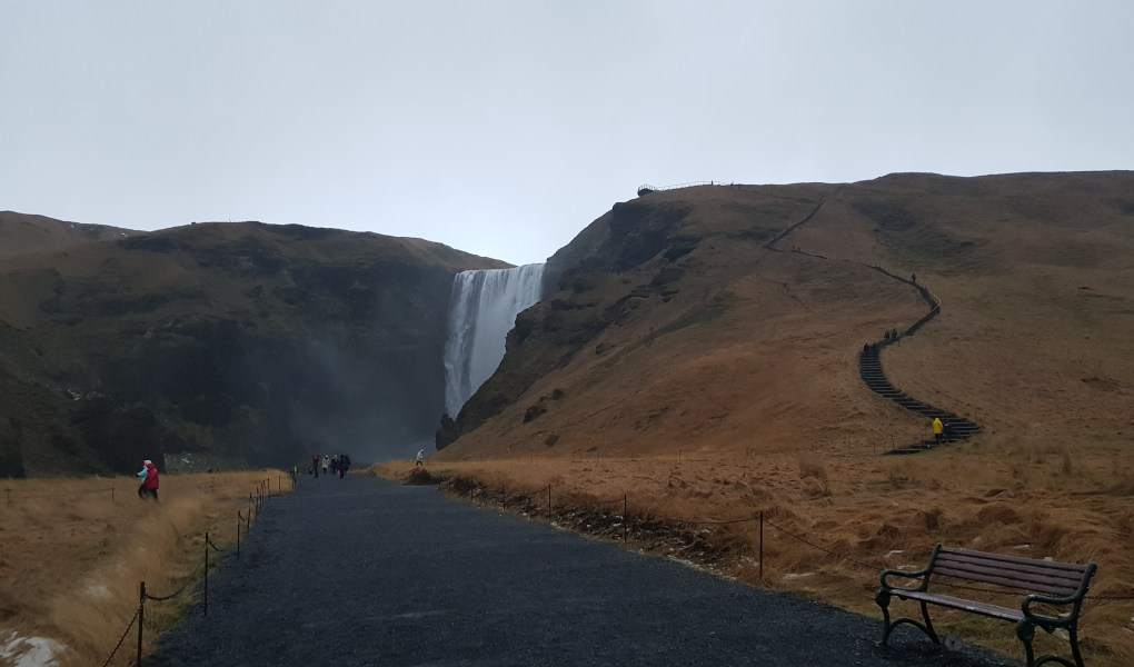A wide dark path leads away from the camera and up to a waterfall in the distance. Either side of the waterfall and large hills and one side has a very steep pathway leading up the hill