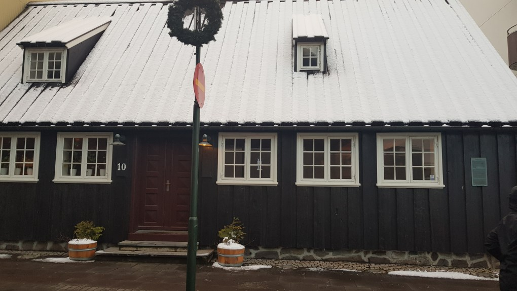 One of the oldest houses standing in Reykjavik. It has a blue corrugated steel wall covering and red door. The roof is white with snow