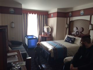 Inside the Newport Bay Club hotel room. A nautical themed room in blue, brown and cream with a ships steering wheel with mouse ears on the bed headboard