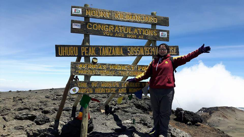 A girl stood at the summit of Kilimanjaro. A sign reads 'Mount Kilimanjaro. Congratulations you are now at Uhuru Peak 5895m'