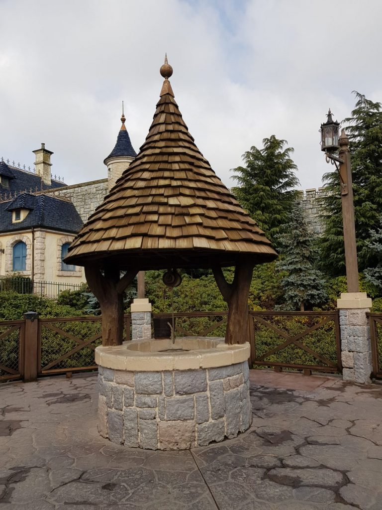 A grey stone wishing well with brown wooden cone roof like the one seen in Snow White