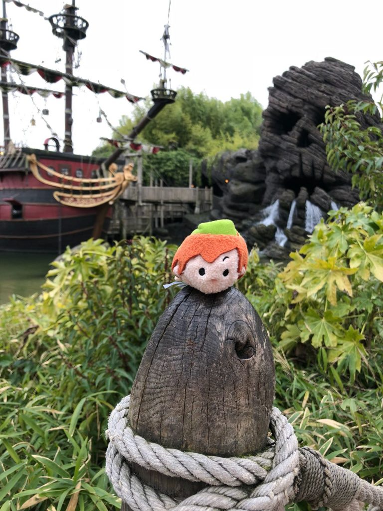Peter Pan Tsum Tsum on a wooden post in front of a red pirate ship and Skull rock