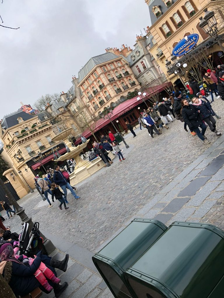 Parisian street scene in front of the Ratatouille ride. A fountain is in the middle of the square with tall buildings around the edge. A restaurant has red awning over the ground floor of the building
