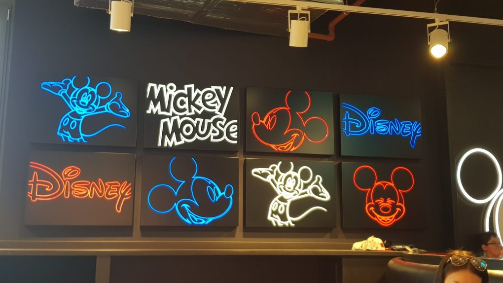 Black squares with neon red, white and blue images of Mickey Mouse and Disney logo found in the Disney cafe