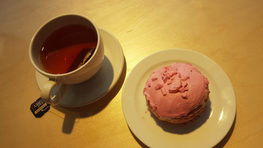 A cup of Earl Grey tea next to a pink lemon meringue donut in the Primarket Cafe