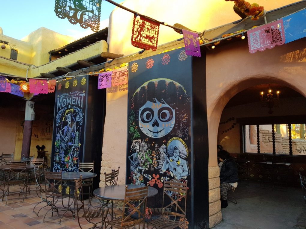 The inside of a courtyard at Fuente del Oro Restaurante. Orange archways line the walls. Colourful flags with cut out shapes are strung up along the walls and across  the middle of the courtyard. Two black panels have colourful pictures of Mexican style sugar skull skeletons.