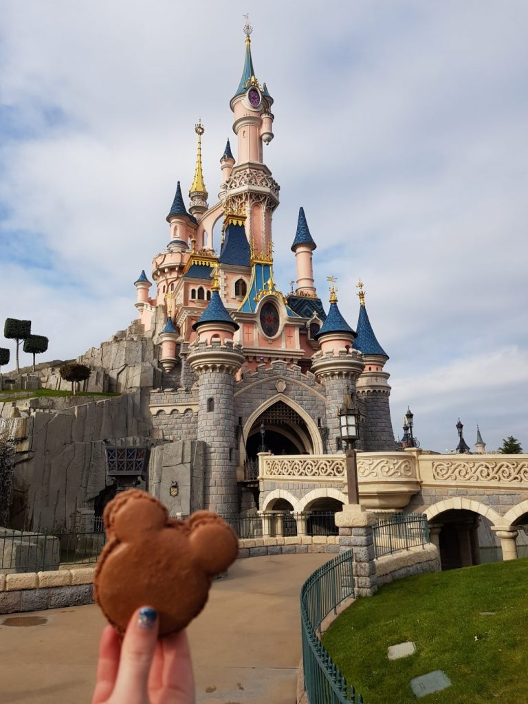 a hand holding a chocolate macaroon in the shape of Mickey's head. Behind is the Disneyland Paris Castle with grey stone walls, a cream bridge, pink turrets and blue roofs