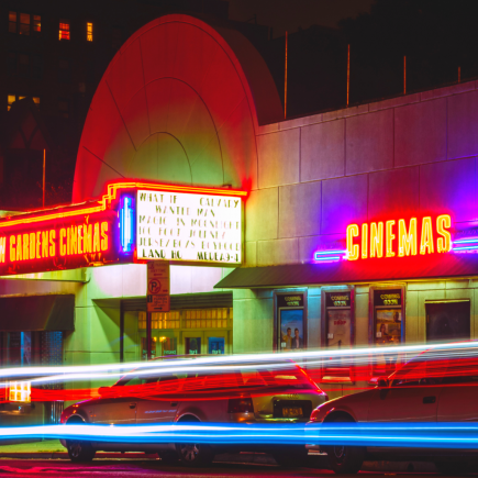 Old fashioned style cinema with retro neon signs showing wanderlust movies