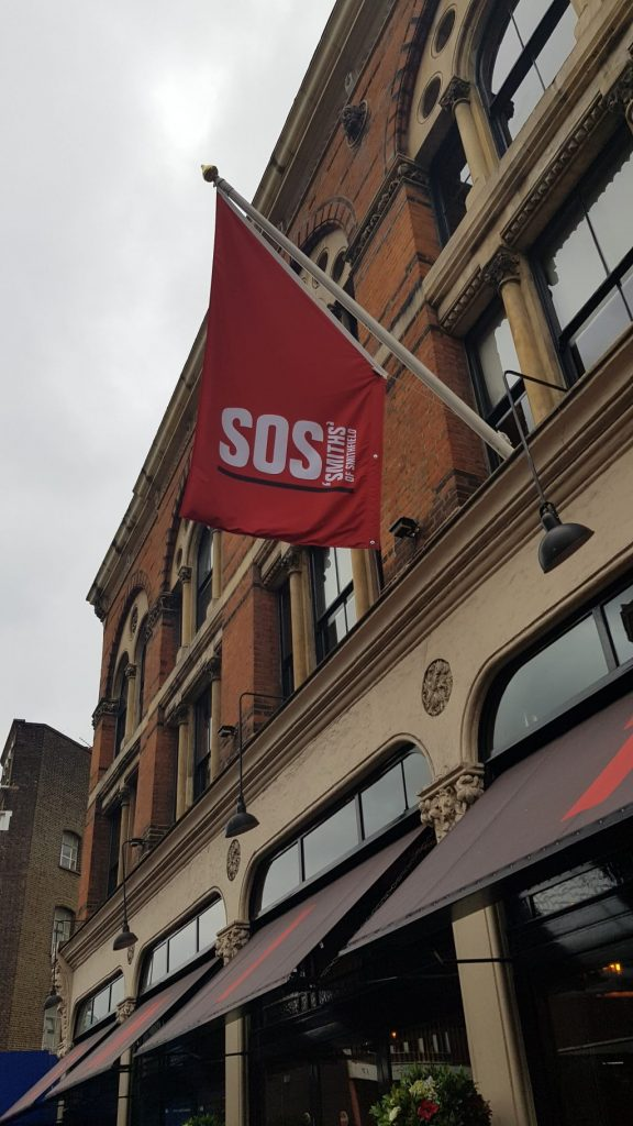 A tall building with a restaurant on the ground floor and black awning. A red flag is hung with white writing saying SOS Smith's of Smithfield. This is the starting location for Lost Souls of the City