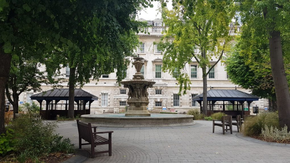 A fountain stands in the middle of a paved square with two wooden shelters either side. Benches are around the fountain and trees around.