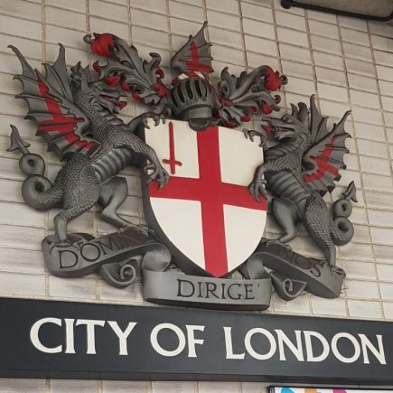 Sign saying City of London with an English flag on a shield being held by two dragons. One of the clues in Hidden City London